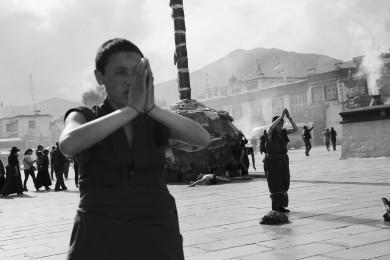 A nun praying at Jokhang square in Lhasa, Tibet.