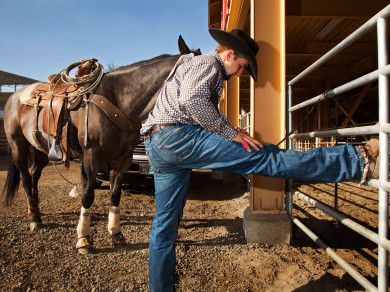 A cowboy stretching before his event at the Pendleton Roundup