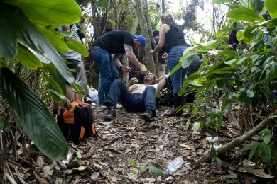 Mr. Yamil Gonzales, 45, is tended by fellow Cuban immigrants after he fainted on a jungle path while walking towards the border with Panama, Colombia, March 28, 2015. For the last three years Panama has experienced a huge migration wave of Cuban, Somalis, Nepalese, Pakistanies and Sri Lankan citizens who first arrive in Ecuador, Brazil or Guyana and then move by land throughout Colombia to arrive in Panama where they get transit visas and then head up north of the continent towards USA.