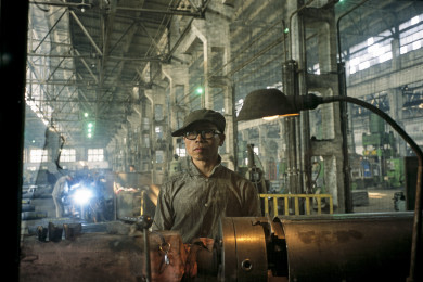 China - Liaoning - Shenyang, Lathe man on assembly line at former weapons plant.