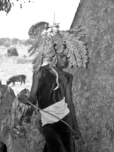 A girl plays with a tree branch in a host community in Garaku, Nigeria.