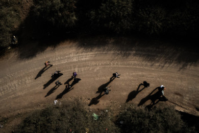 Syrian refugees walk on the dirt track.