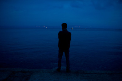 A refugee looks towards Turkey after arriving on the Greek island of Lesbos.