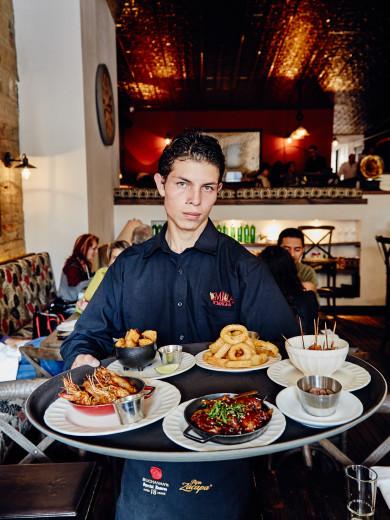 Server with a tray of bar food Chef Daniel Castano's Restaurant Gordo