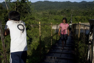 U´wa people walk over a bridge called Hamaca or the Hammock over the Cobaria river. A three hundred meter long hunging bridge that conects communities on both sides of the river Colombia, september 2, 2014. The U´wa indigenous group have being fighting oil exploration and extraction on their territory for decades, since they they think oil is mother´s land blood and therefore it is forbiden to bleed her out. On March 25th of this year The National Liberation Army, ELN, (spanish) attacked with explosives the pipeline, managed and owned by Ecopetrol, in Puente China. The indigenous group stopped workers from repairing the duct for a couple of months rendering the company a huge loss.