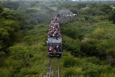 Illegal immigrants ride a cargo train towards the city of Ixtepec, Mexico, September 22, 2011. Thousands of migrants ride these trains every year in Mexico in hopes to get closer to the border in the USA.