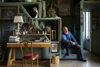 """BARNABA FORNASETTI beside the work station in the studio with the red piano. Fornasetti desk """"Riga e squadra"""" (ruler and square) by Barnaba Fornasetti with several different Fornasetti small objects on it and work tools . On the top right shelf: a Fornasetti obelisk lamp with the décor of the butterflies. Over this obelisk lamp: a Fornasetti ceramic cat"""