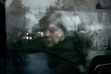 A woman rides an early morning bus in Milan. November 2012.